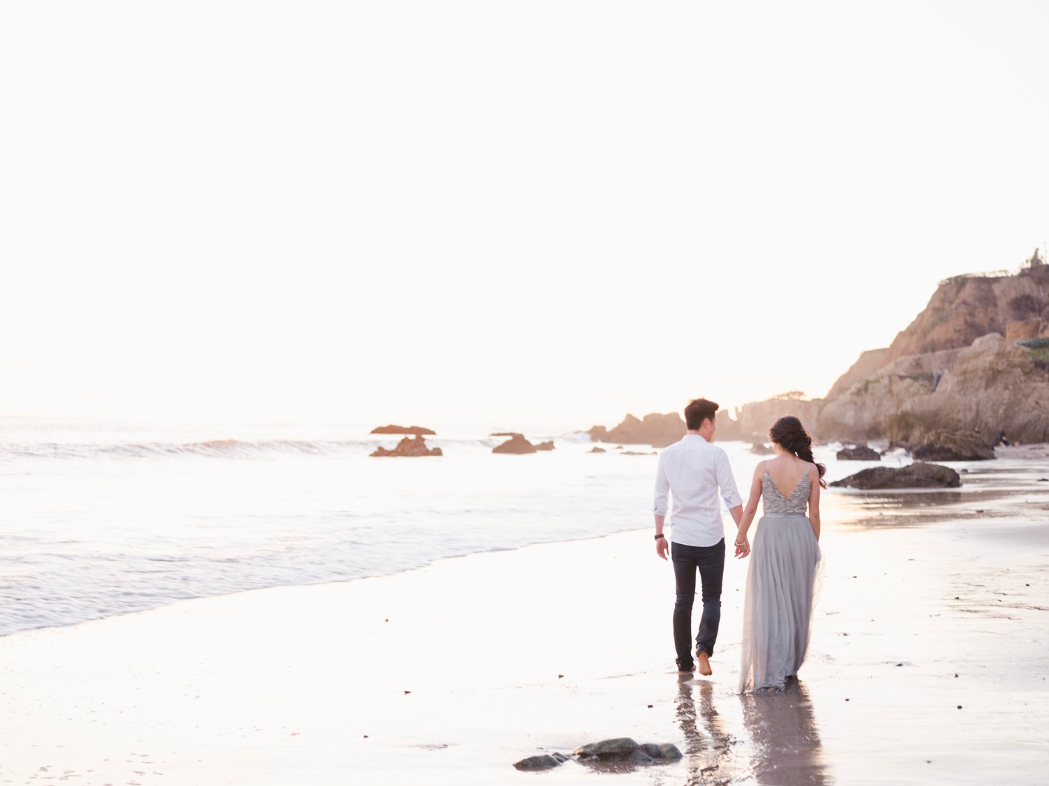 Couple in formal attire walking down the beach holding hands