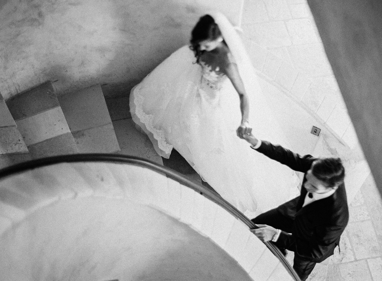 Black and white photo of newlyweds on spiral staircase