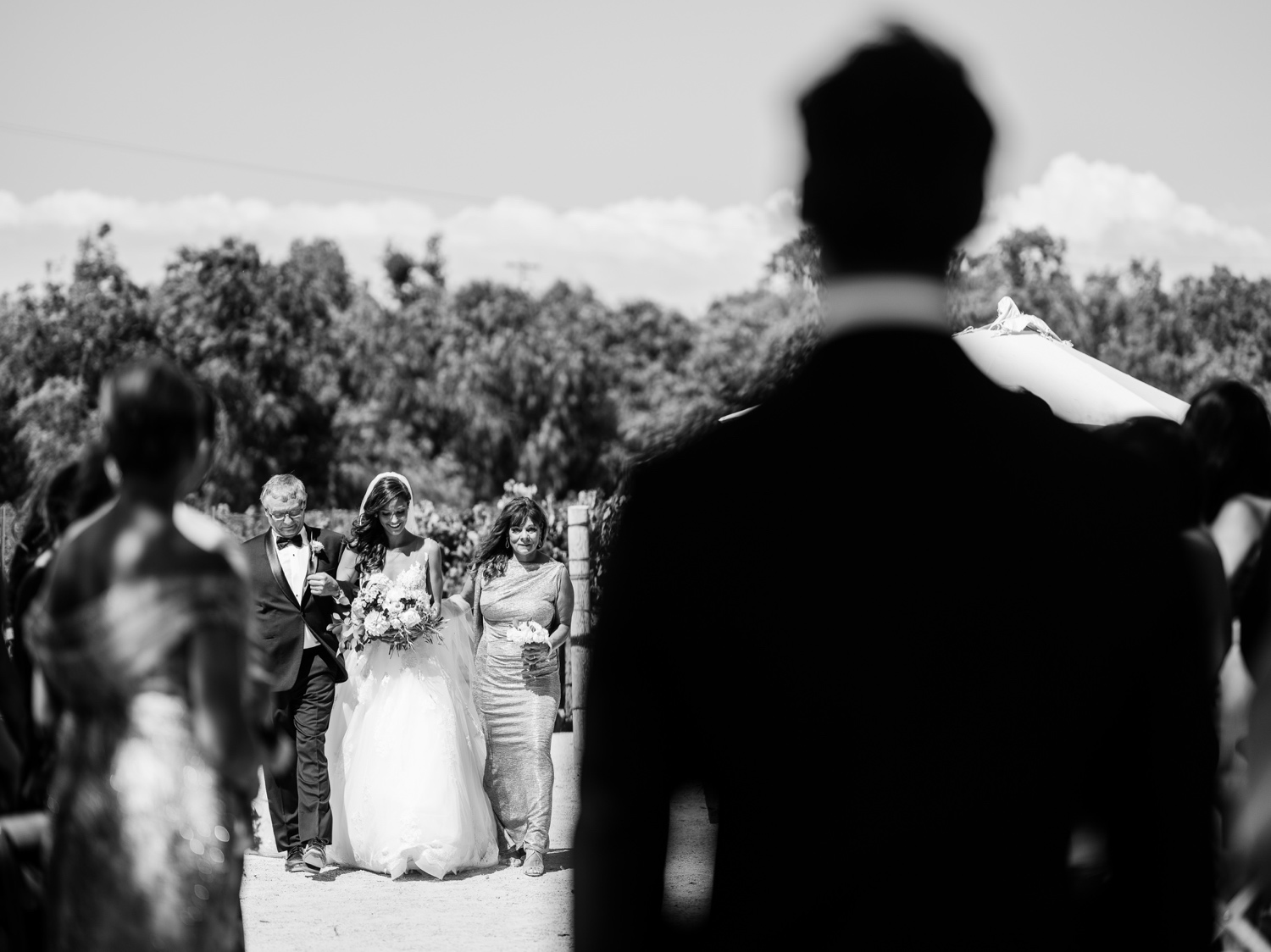 Black and white photo of groom watching his bride walk down the aisle