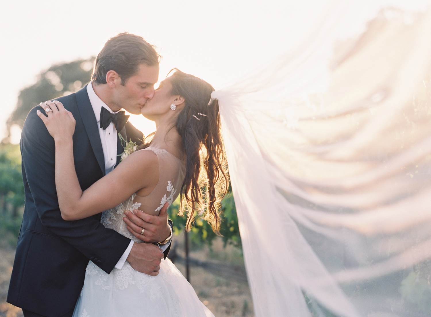 Newlyweds kissing at sunset with veil catching in the wind