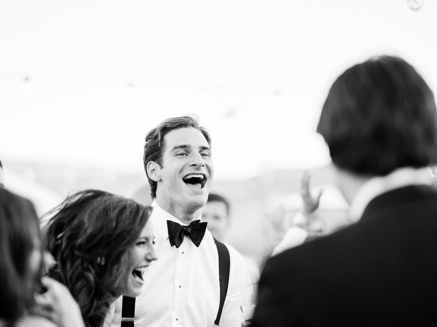 Black and white wedding photo of bride and groom laughing during reception