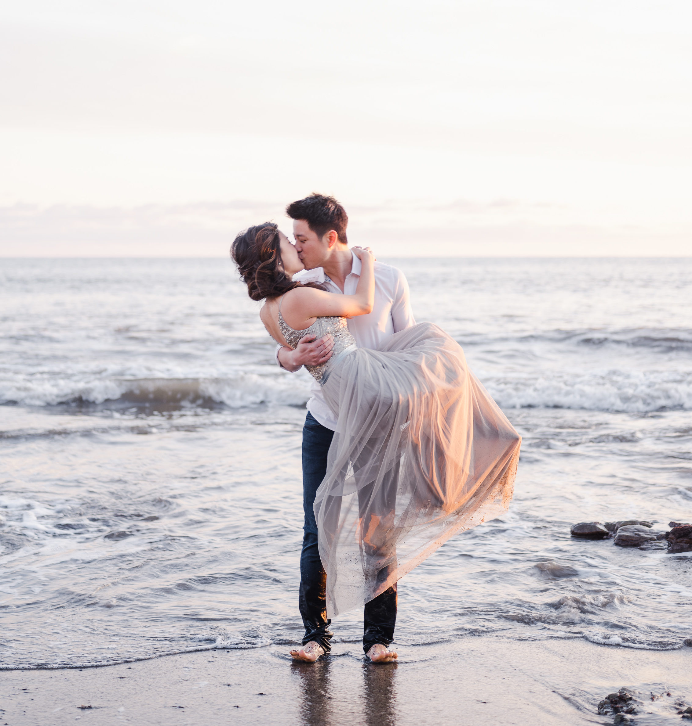 Man holding woman in his arms kissing on the beach in the waves