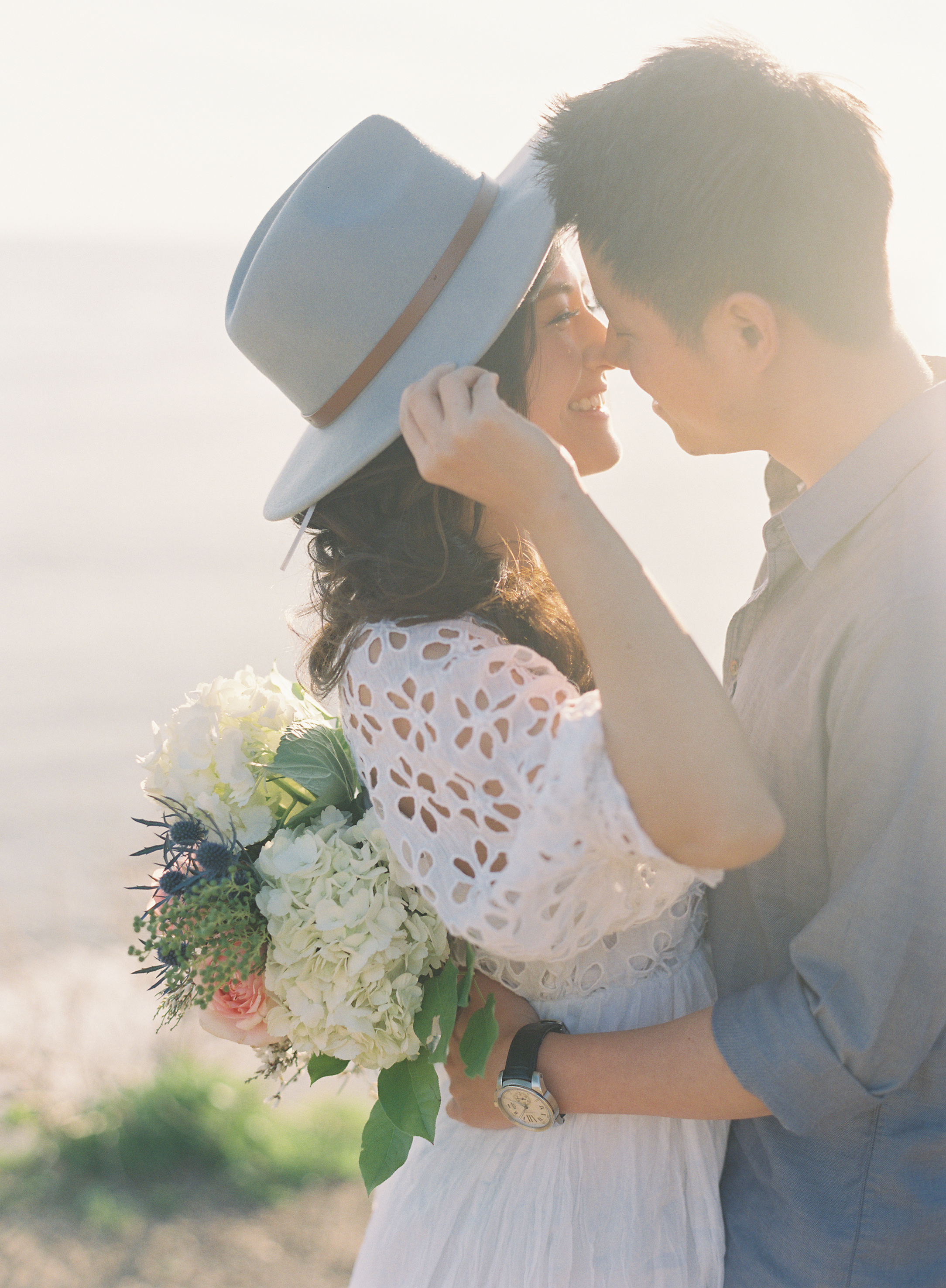 Couple about to kiss with sunset in the background and woman holding onto hat, man holding white and pink flowers