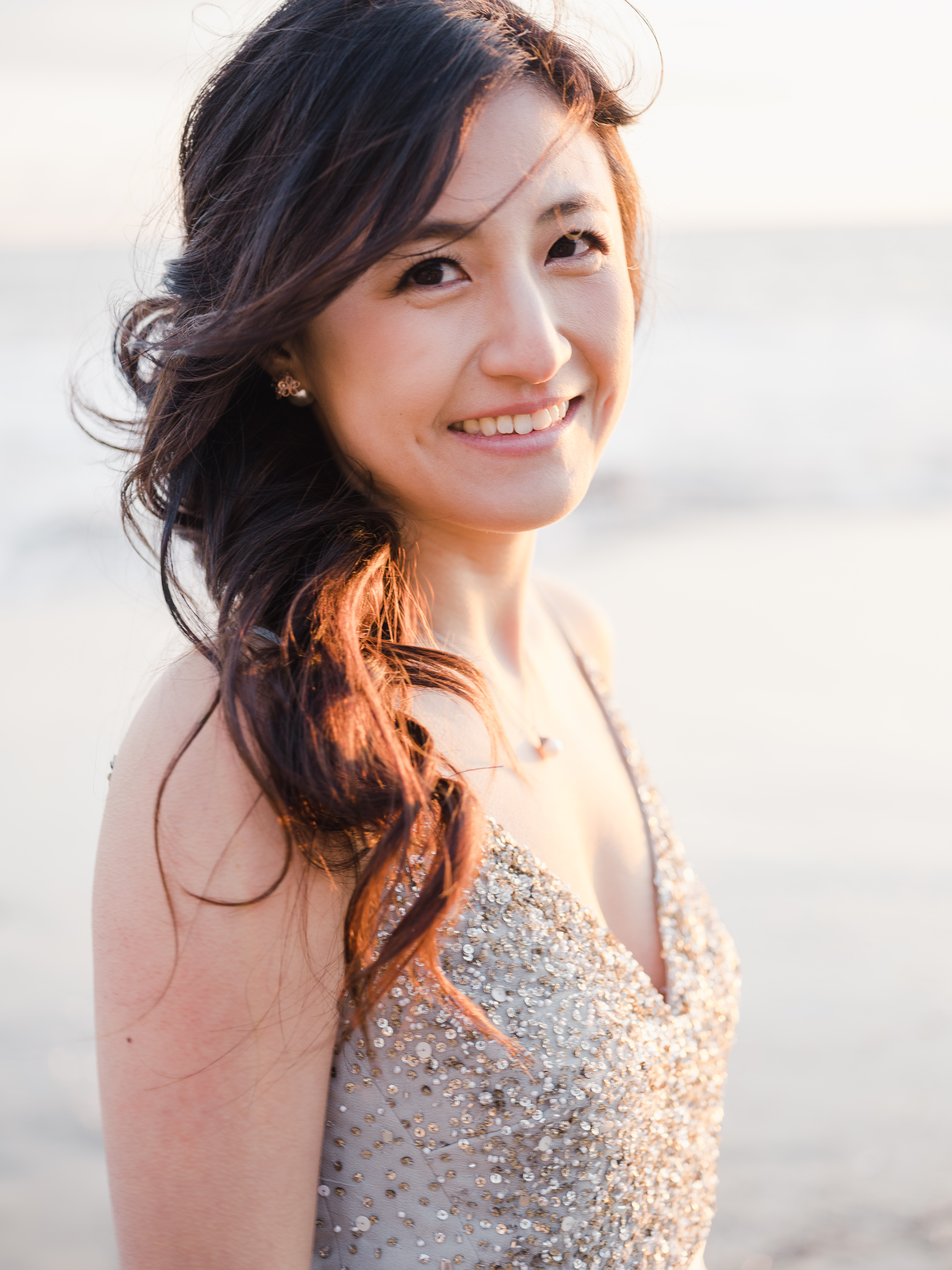 Woman in a beaded dress smiling at the camera on the beach
