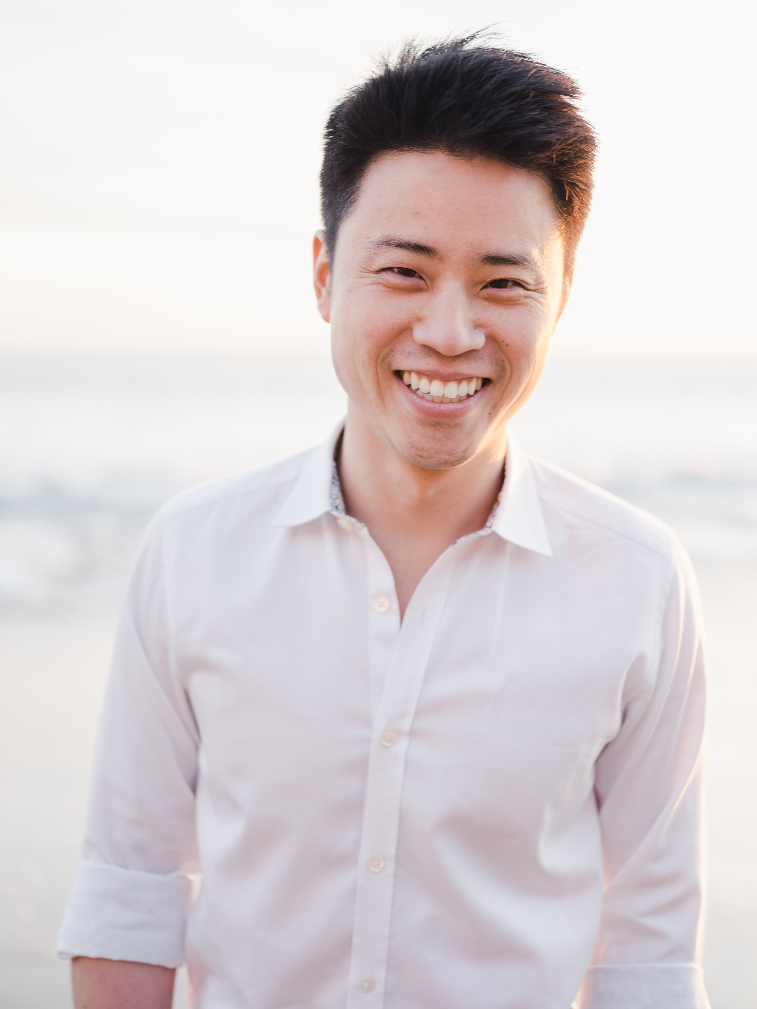 Man in a button down shirt smiling at the camera on the beach