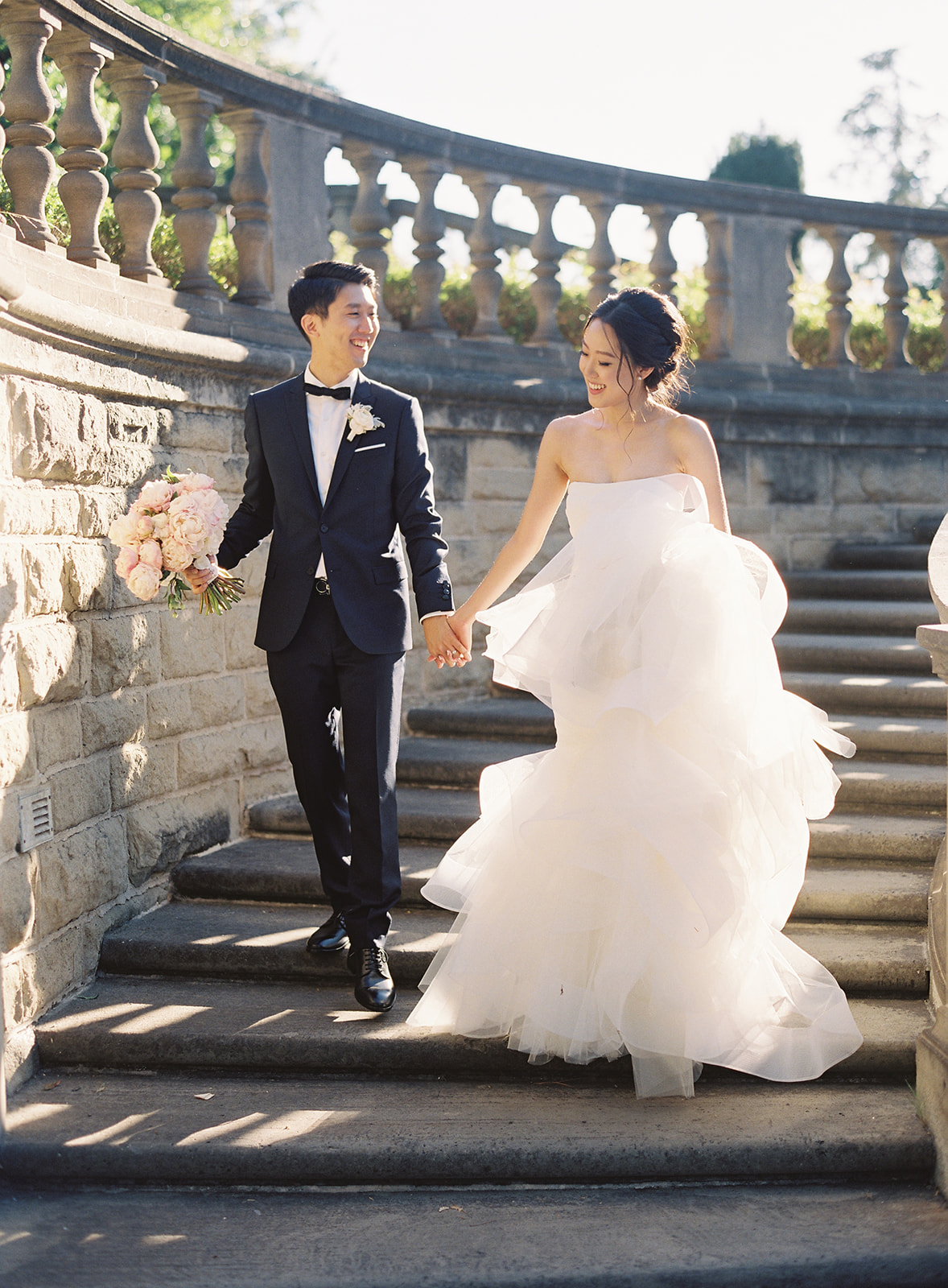 Bride and Groom walking down cement outside staircase