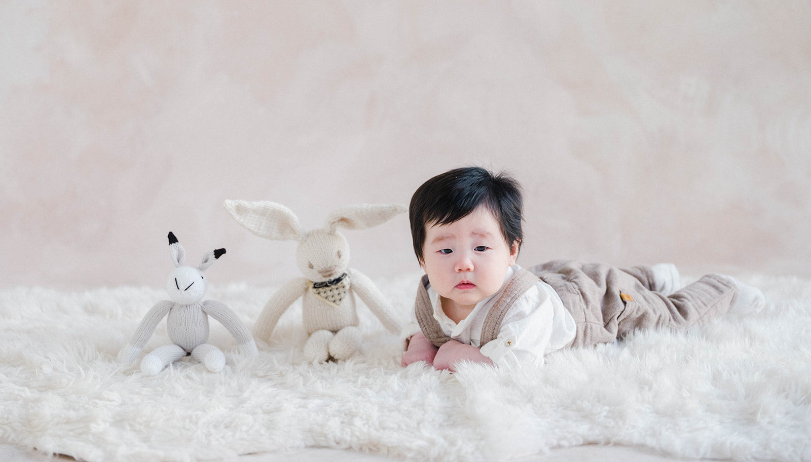 baby on his tummy next to two stuffed animal bunnies