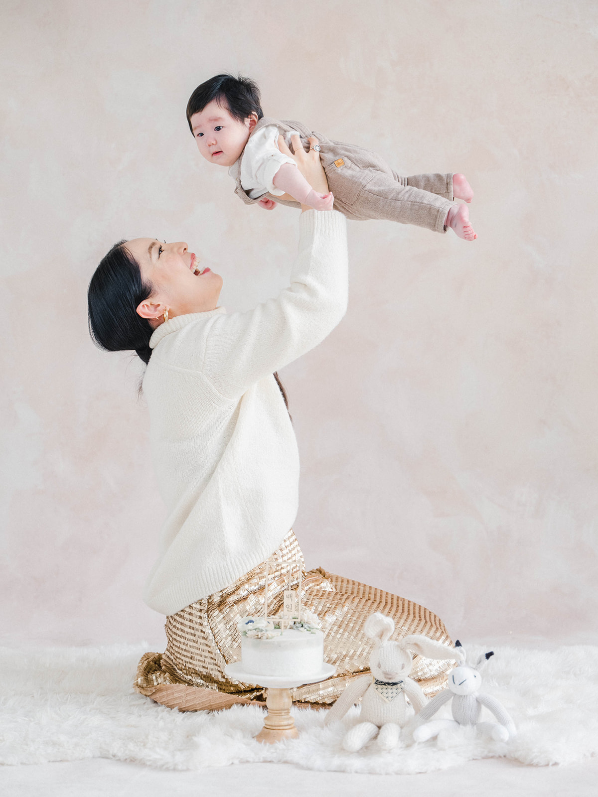 Mom kneeling and holding baby up high above her