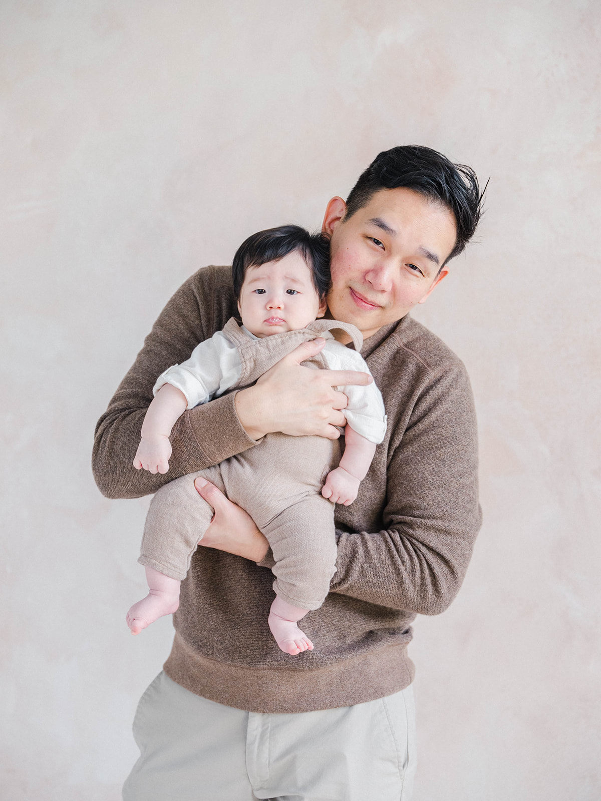 dad holding baby in front of him and facing camera
