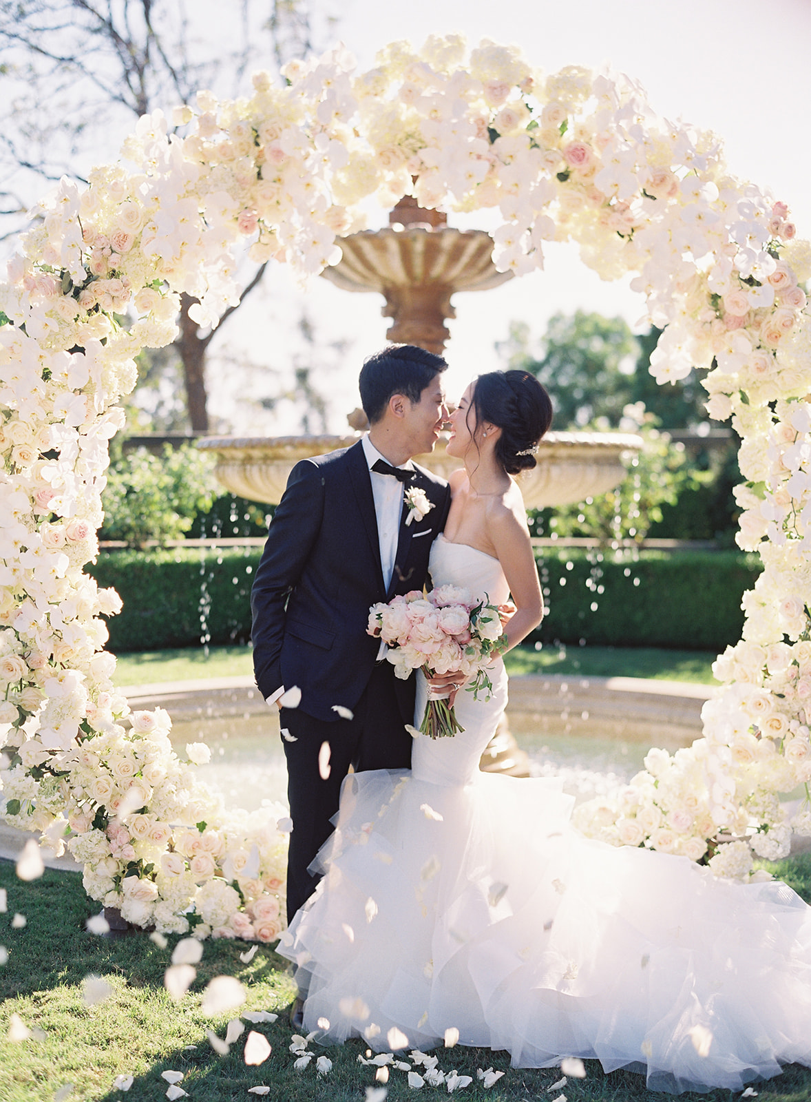 Couple under a life size floral arch holding each other and laughing
