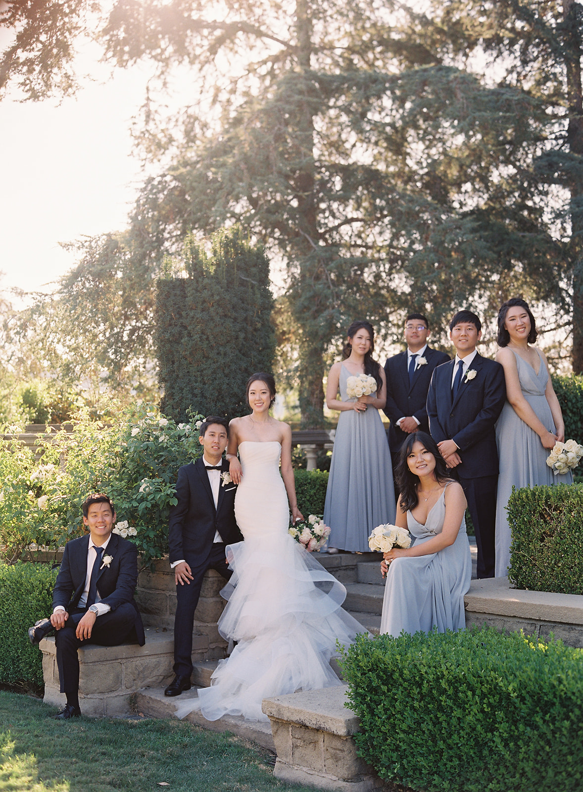 Photo of bridal party surrounding bride and groom and coupled together on stairs and positioned in different heights