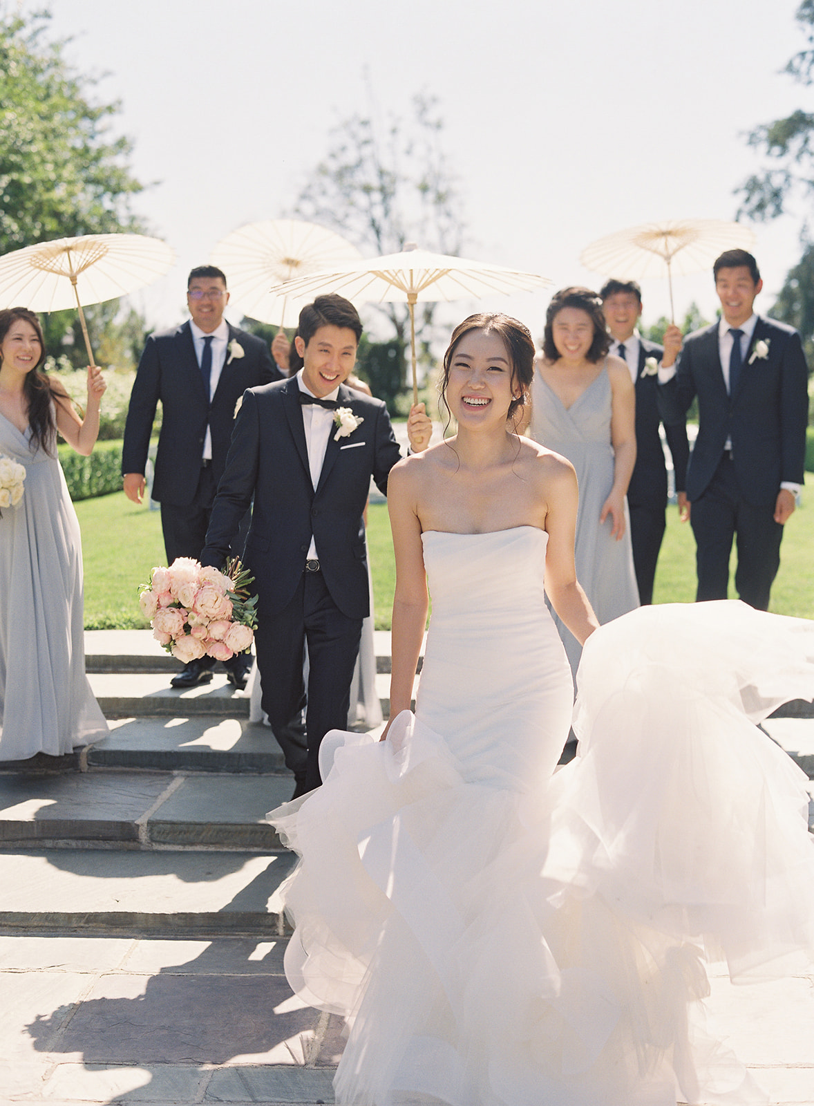 Bridal party holding paper umbrellas walking after bride