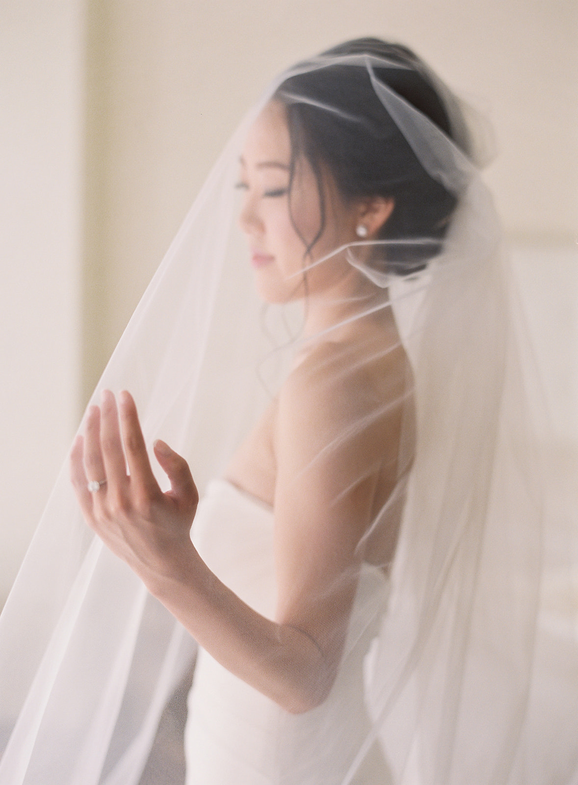 Bride under her long veil in a side profile shot