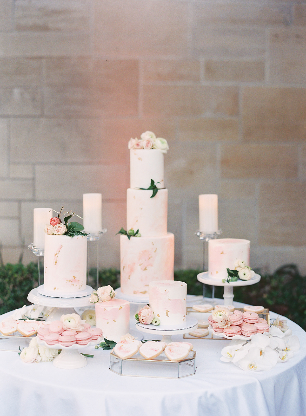 Marbled pink and white wedding cakes in multiple sizes on a table
