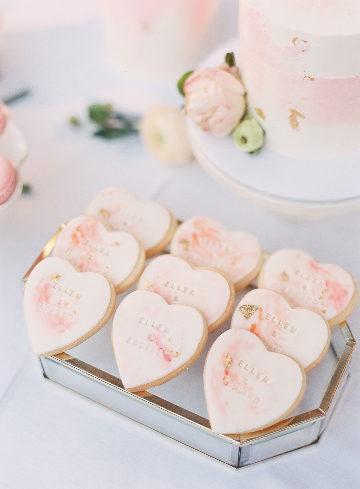 Close up of heart shaped cookies with bride and grooms name stamped in them