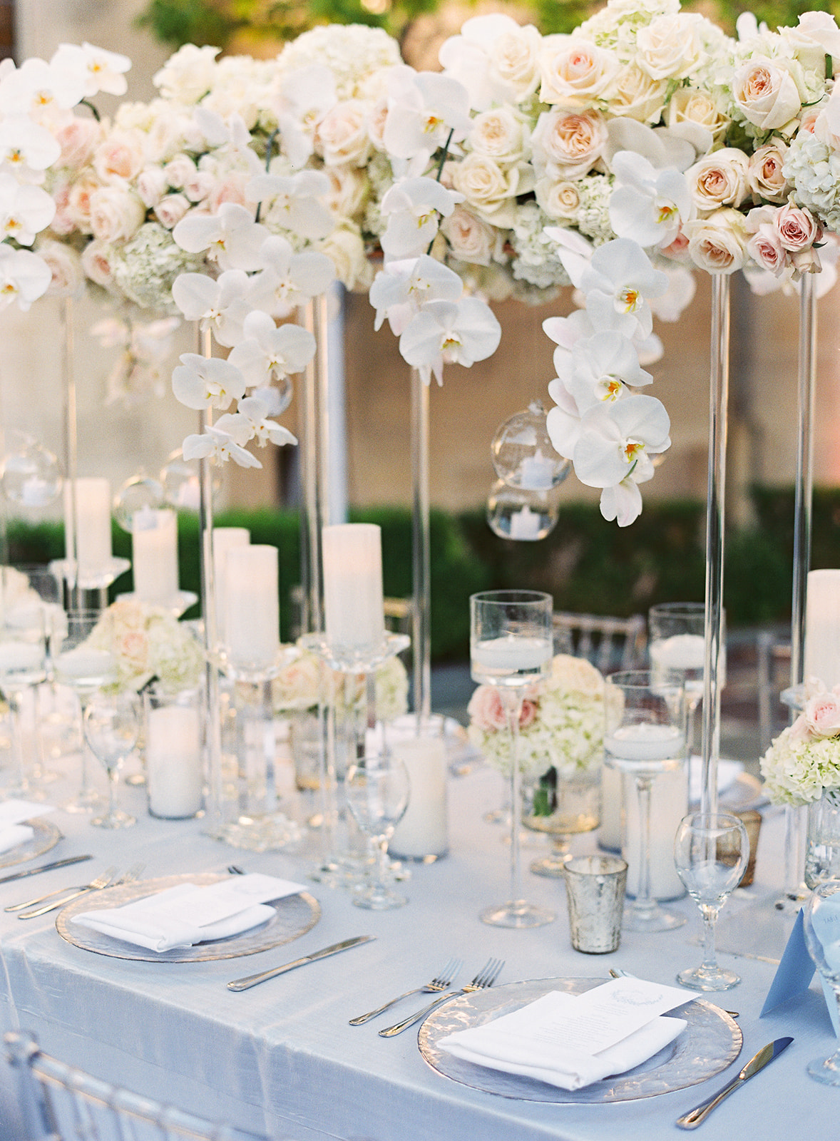 close up shot of table setting with light blue tablecloth and white orchid florals cascading down