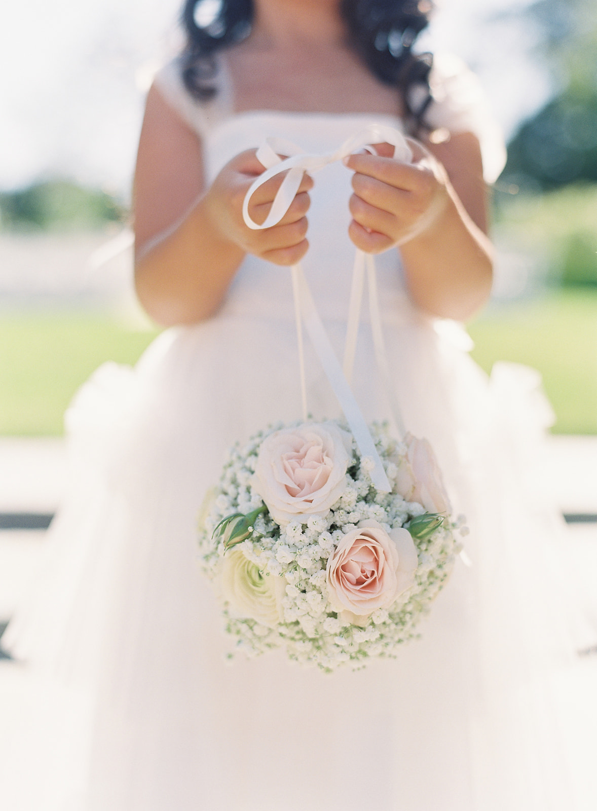 Close up of flower girl holding her round floral bouquet
