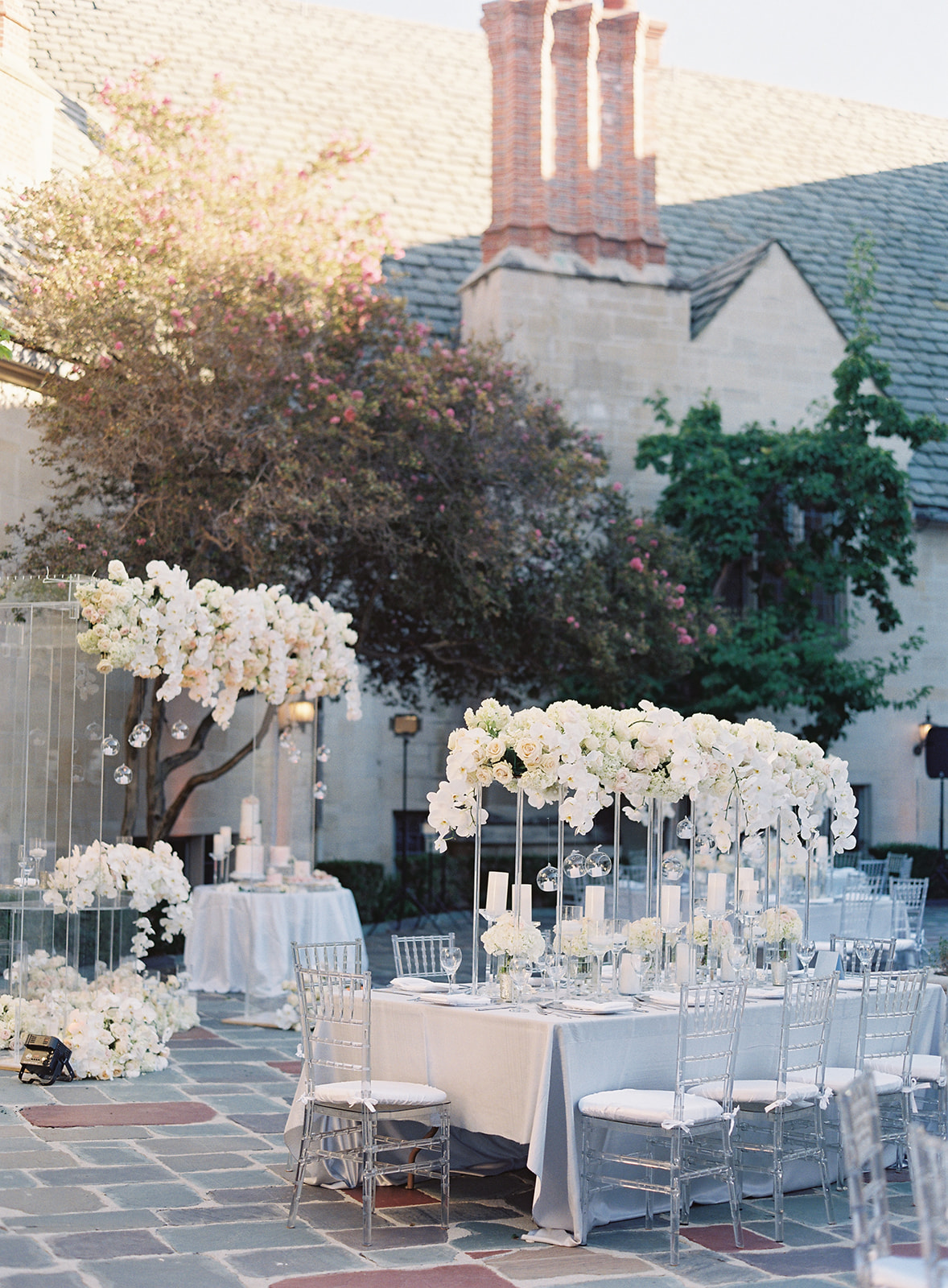 Photo of reception tables with clear chairs and floral centerpieces cascading down towards tables