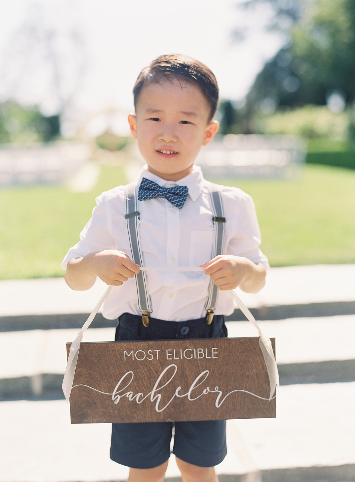 "Ring bearer holding wood sign that reads ""most eligible bachelor"""