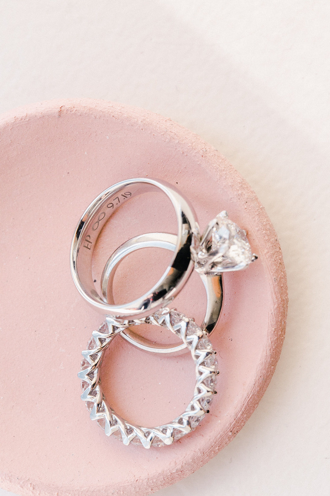 Close up of wedding rings/bands in pink dish