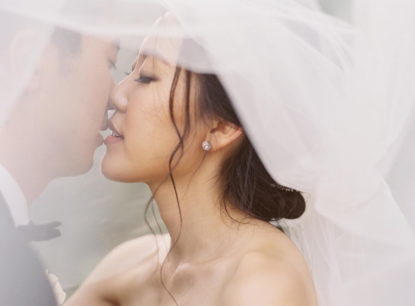 bride and groom kissing under brides veil