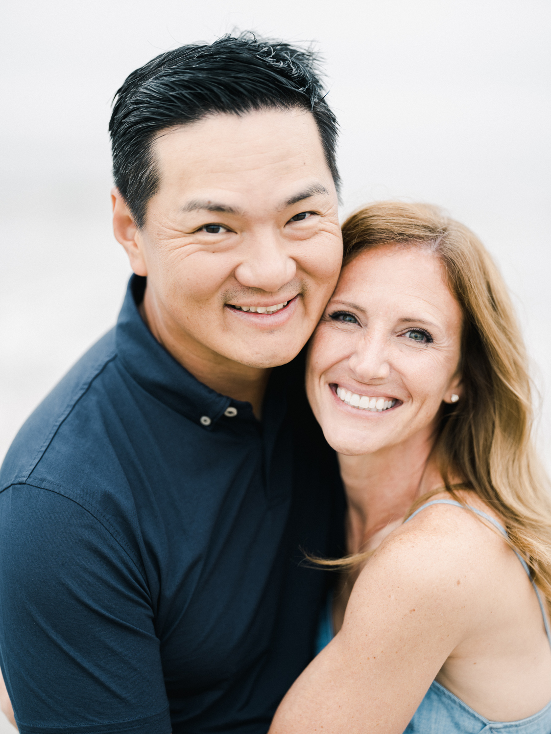 Couple holding one another at the beach and looking into camera