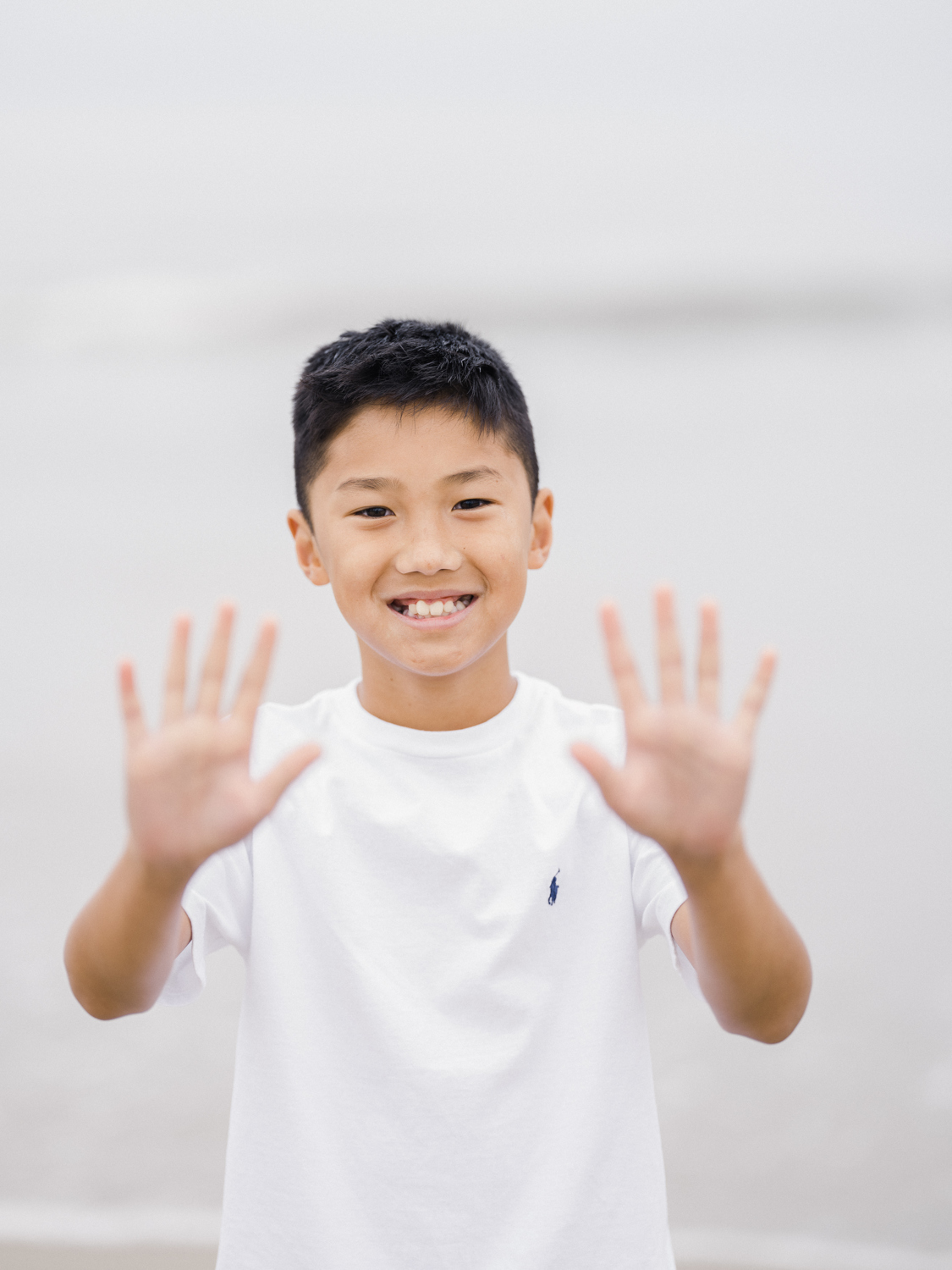 Boy standing on beach holding up 10 fingers