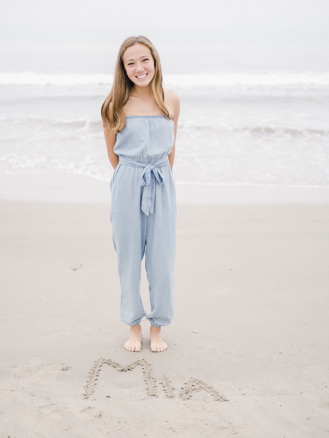 Girls standing on beach with her name written in the sand in front of her