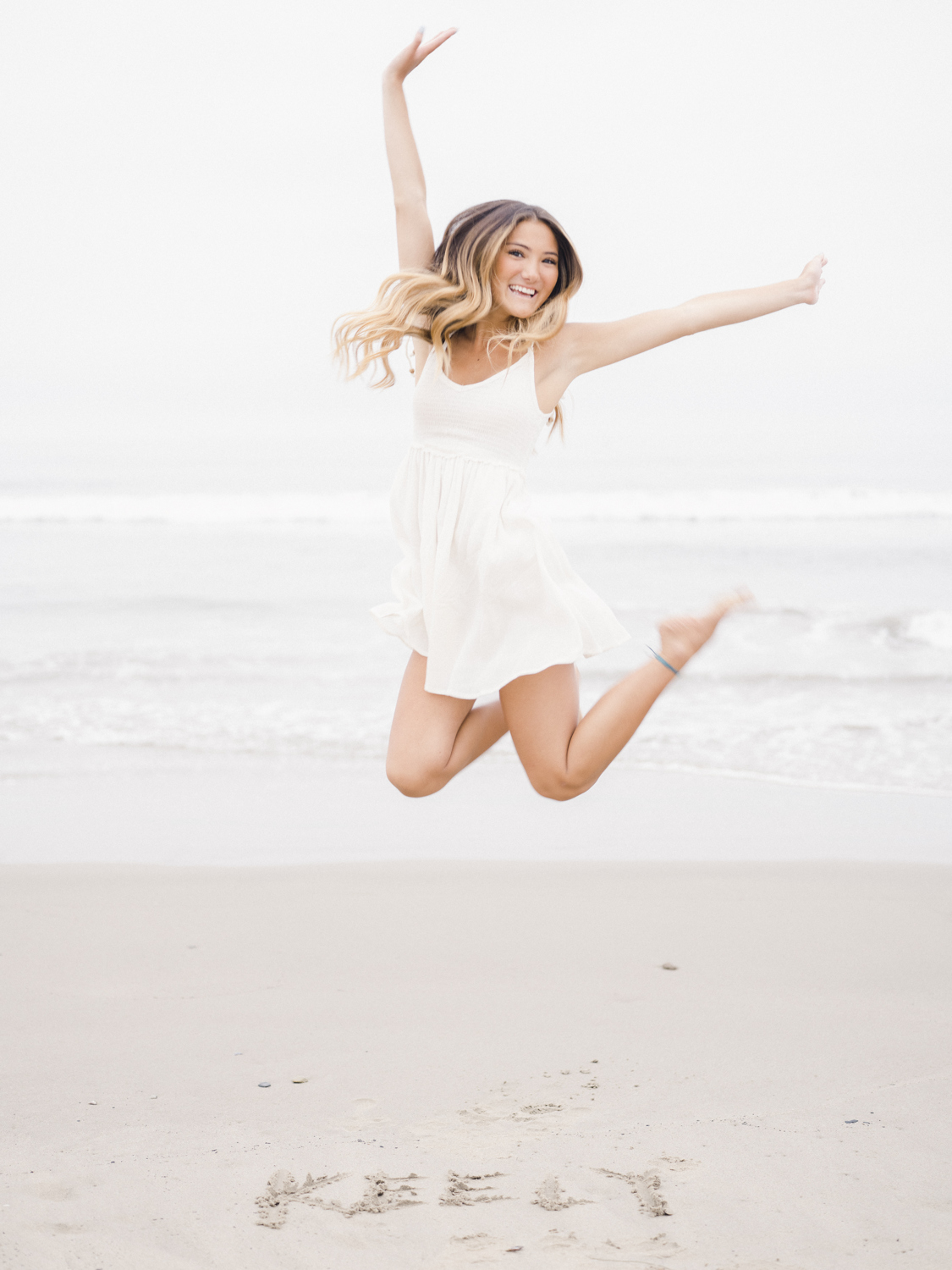 Girl at the beach jumping up in the air with her name written in the sand in front of her
