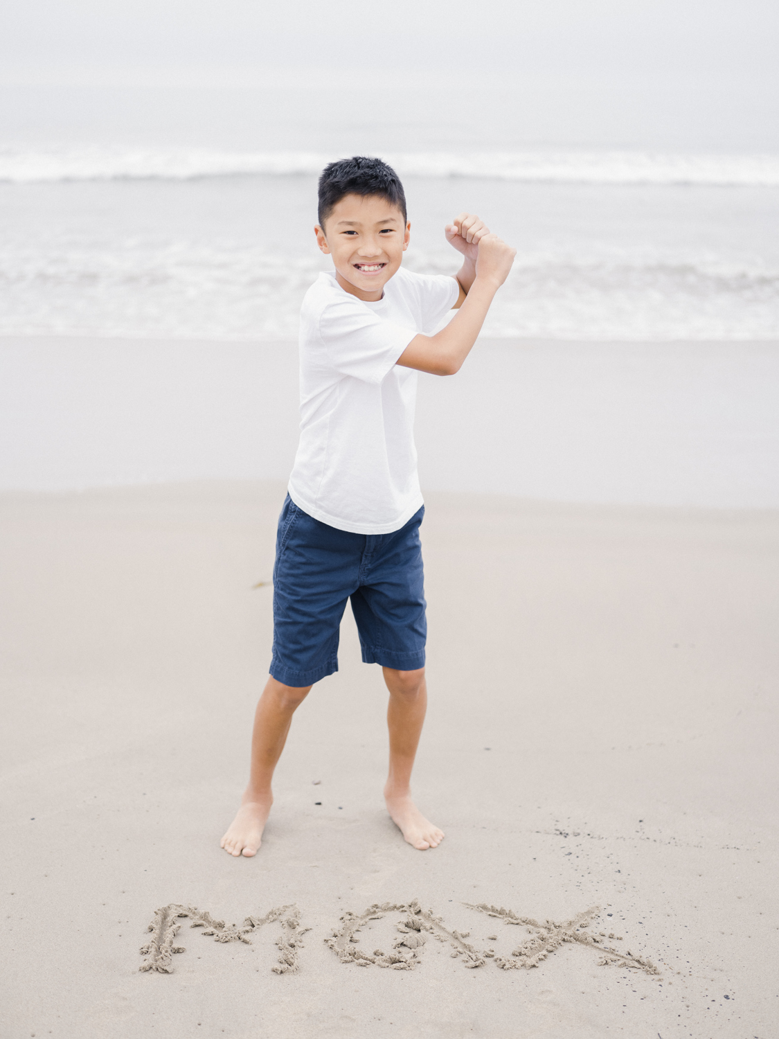 Boy standing on the beach holding his hands like he's holding a  baseball bat
