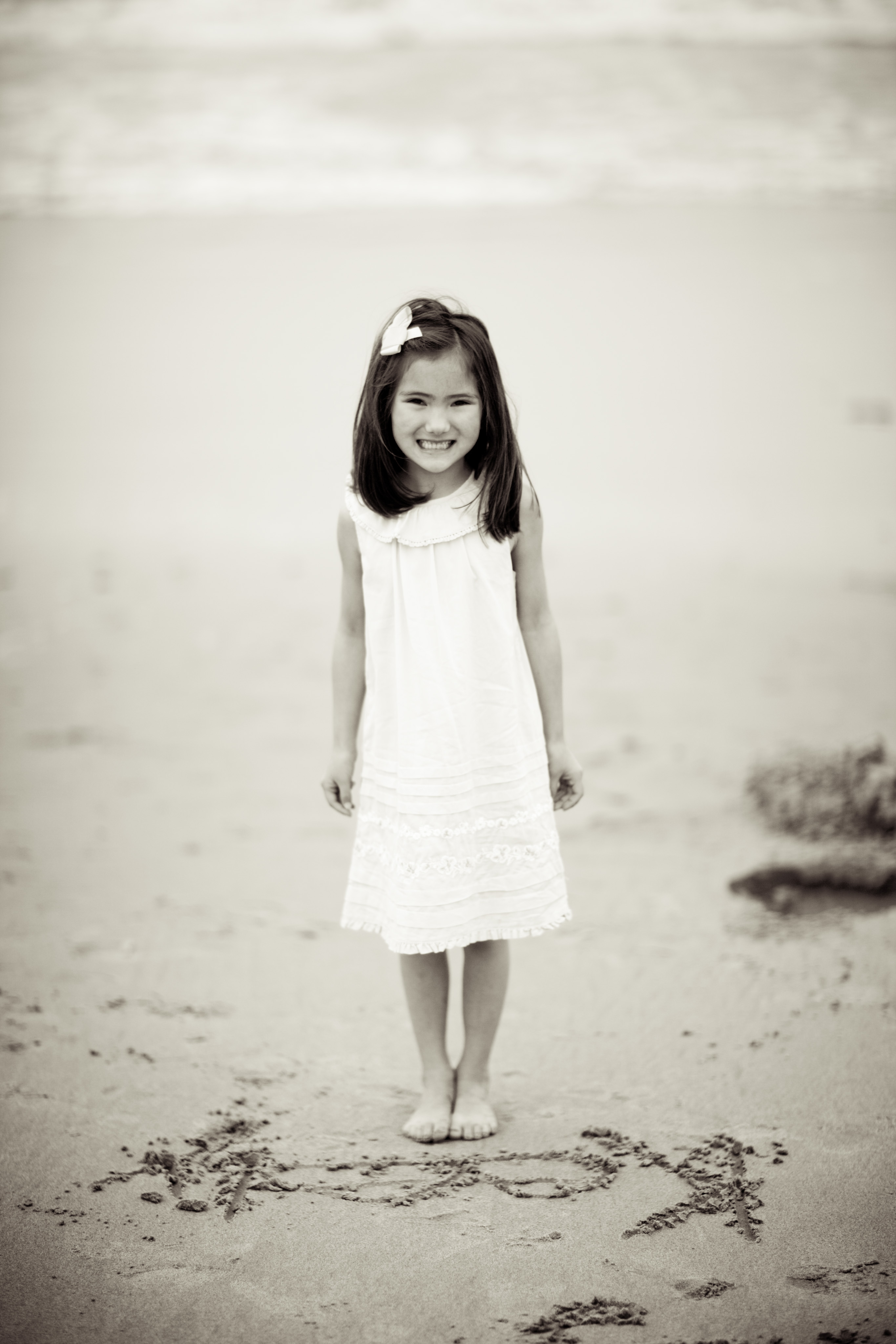 black and white picture of girl in white dress standing on the beach with her name written in the sand in front of her