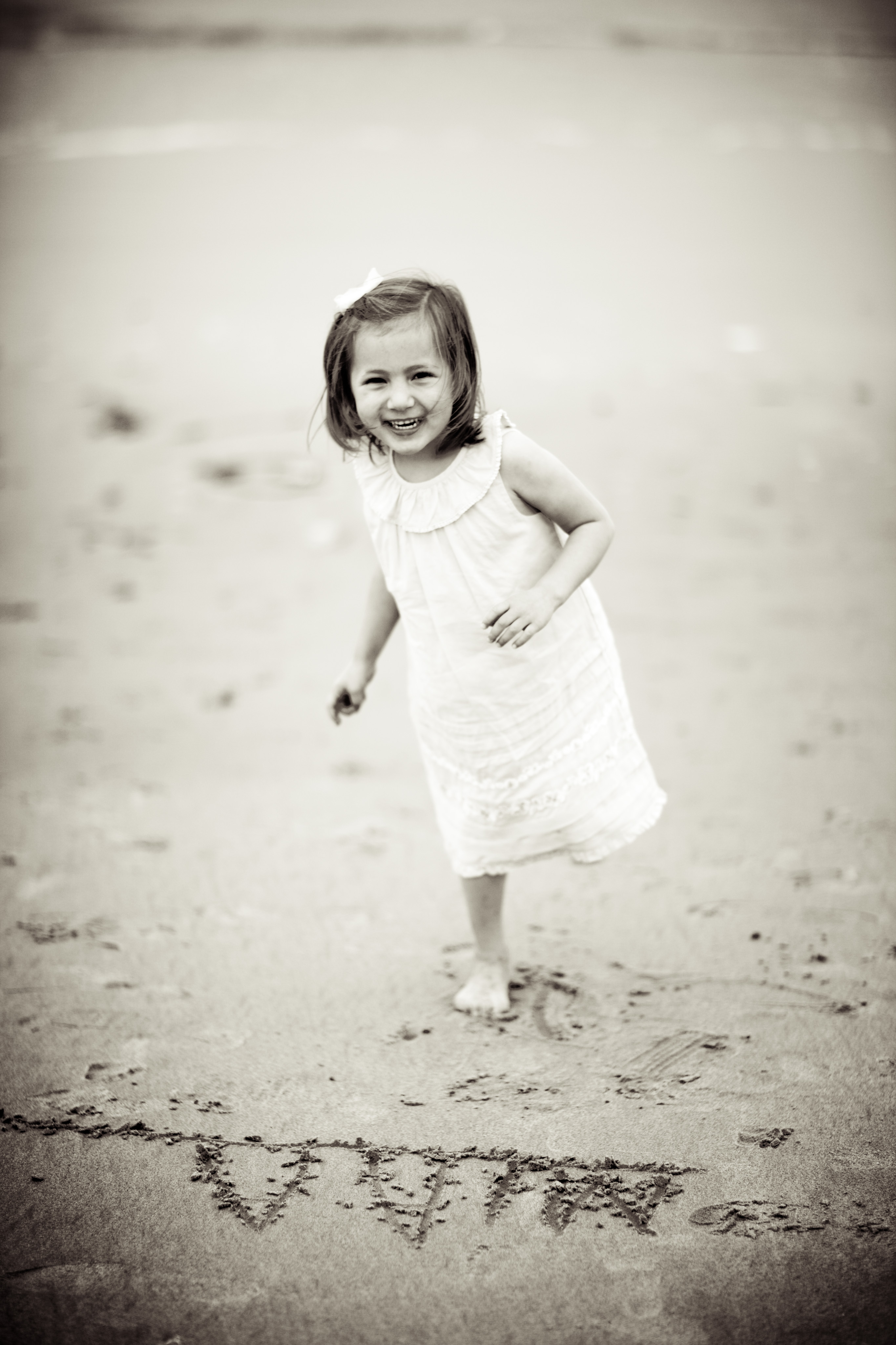 black and white photo of little girl standing on the beach with her name written in the sand in front of her