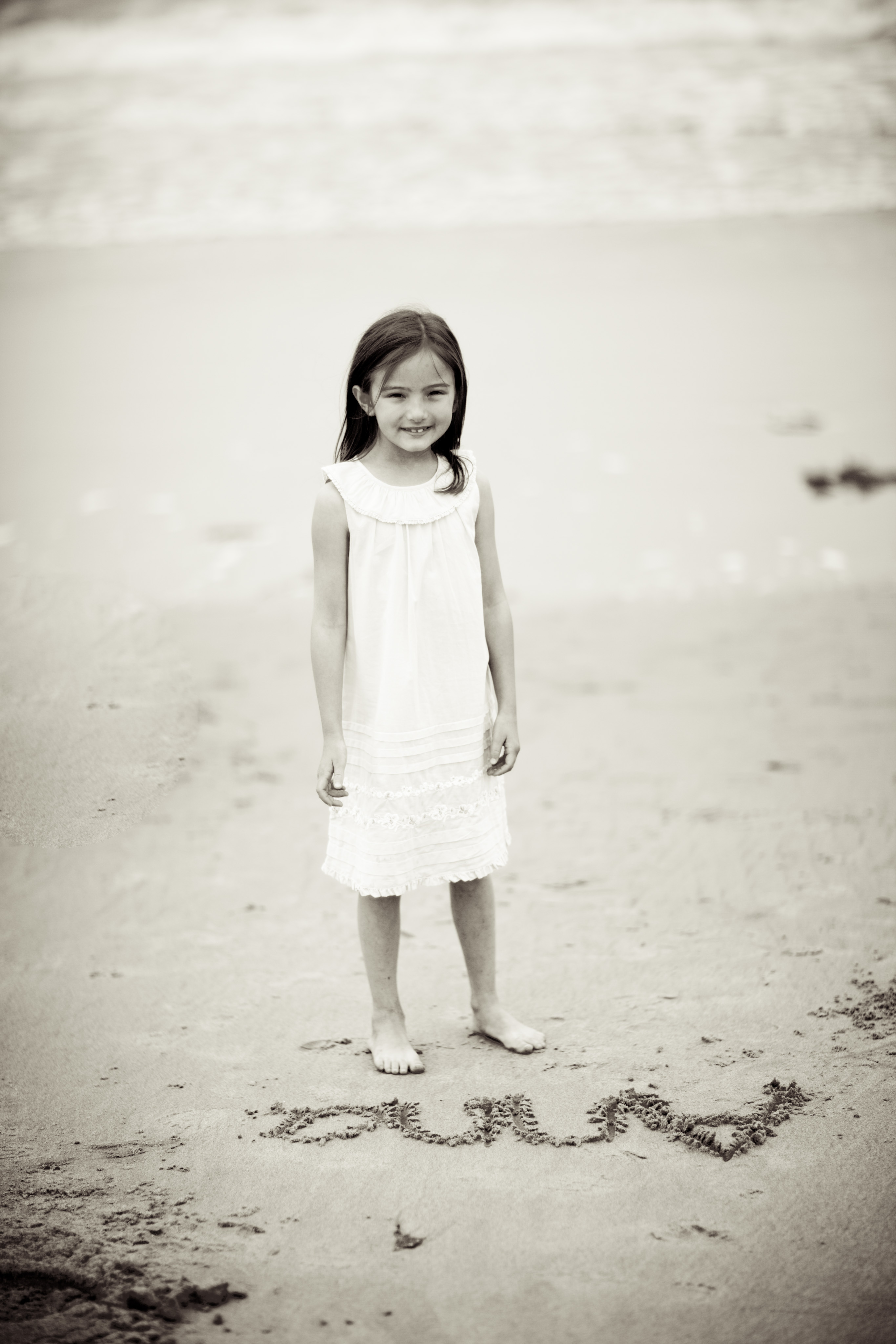black and white picture of girl standing on the beach with her name written in the sand in front of her