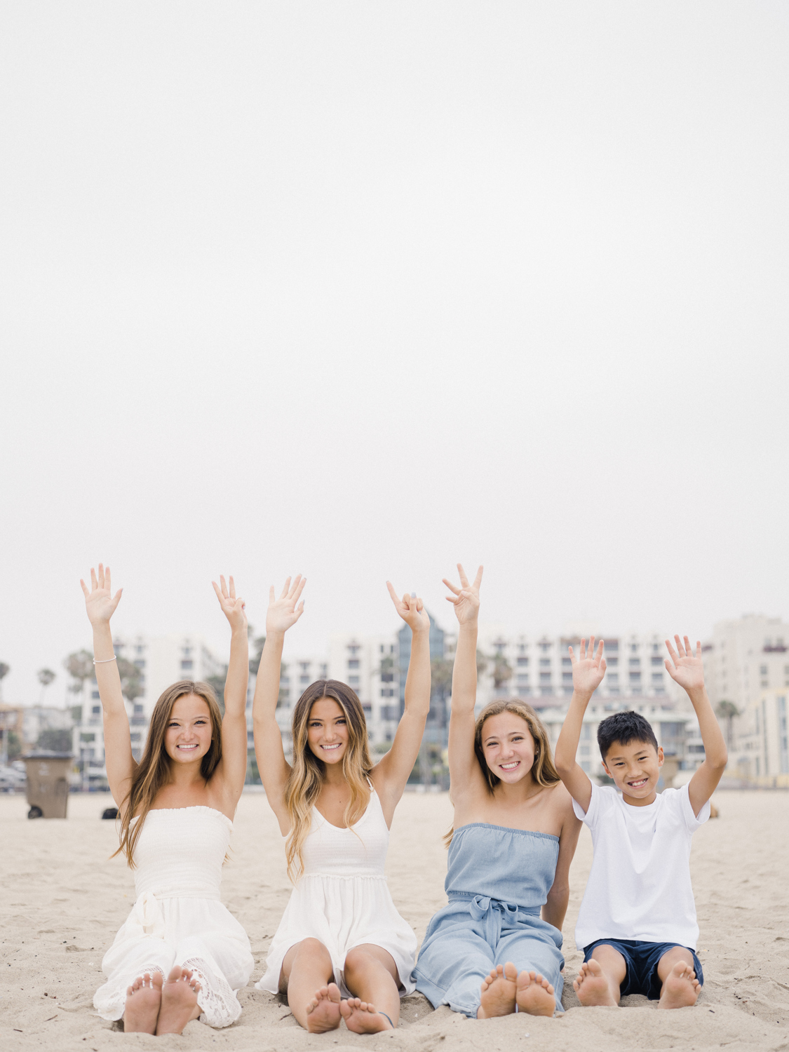 Four siblings sitting on the beach with their hands in the air