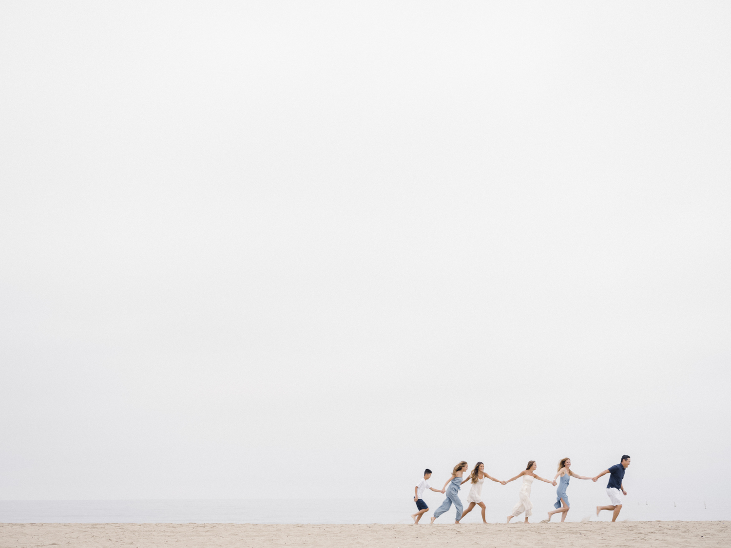 Photo of family holding hands in a single file line running on the beach together