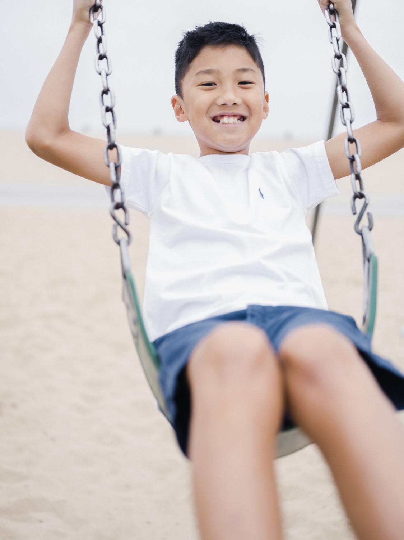 Boy on a swing on the beach