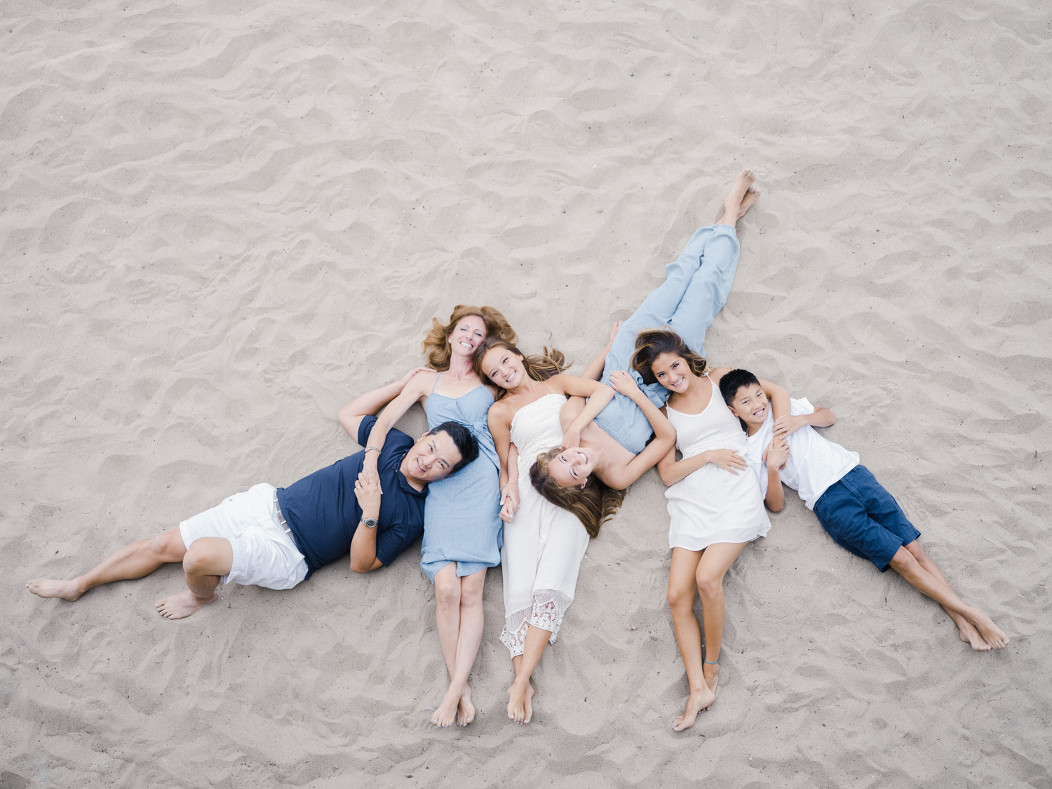 Family of six lying down on the sand looking up at the camera smiling
