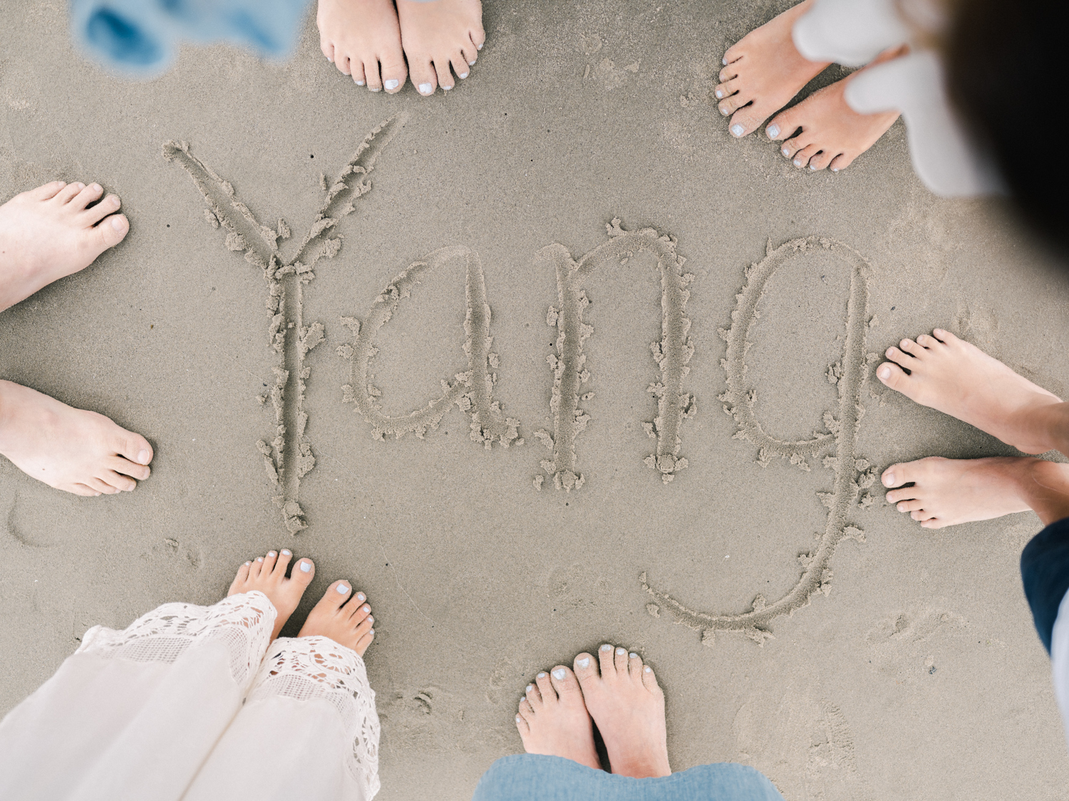 """Overhead shot of feet and the word """"yang"""" spelled out in the sand"""