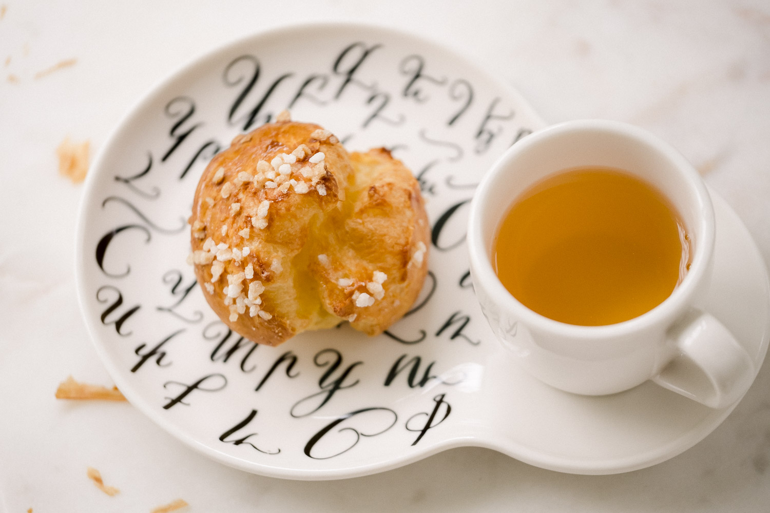 puff pastry on a saucer next to a cup of tea