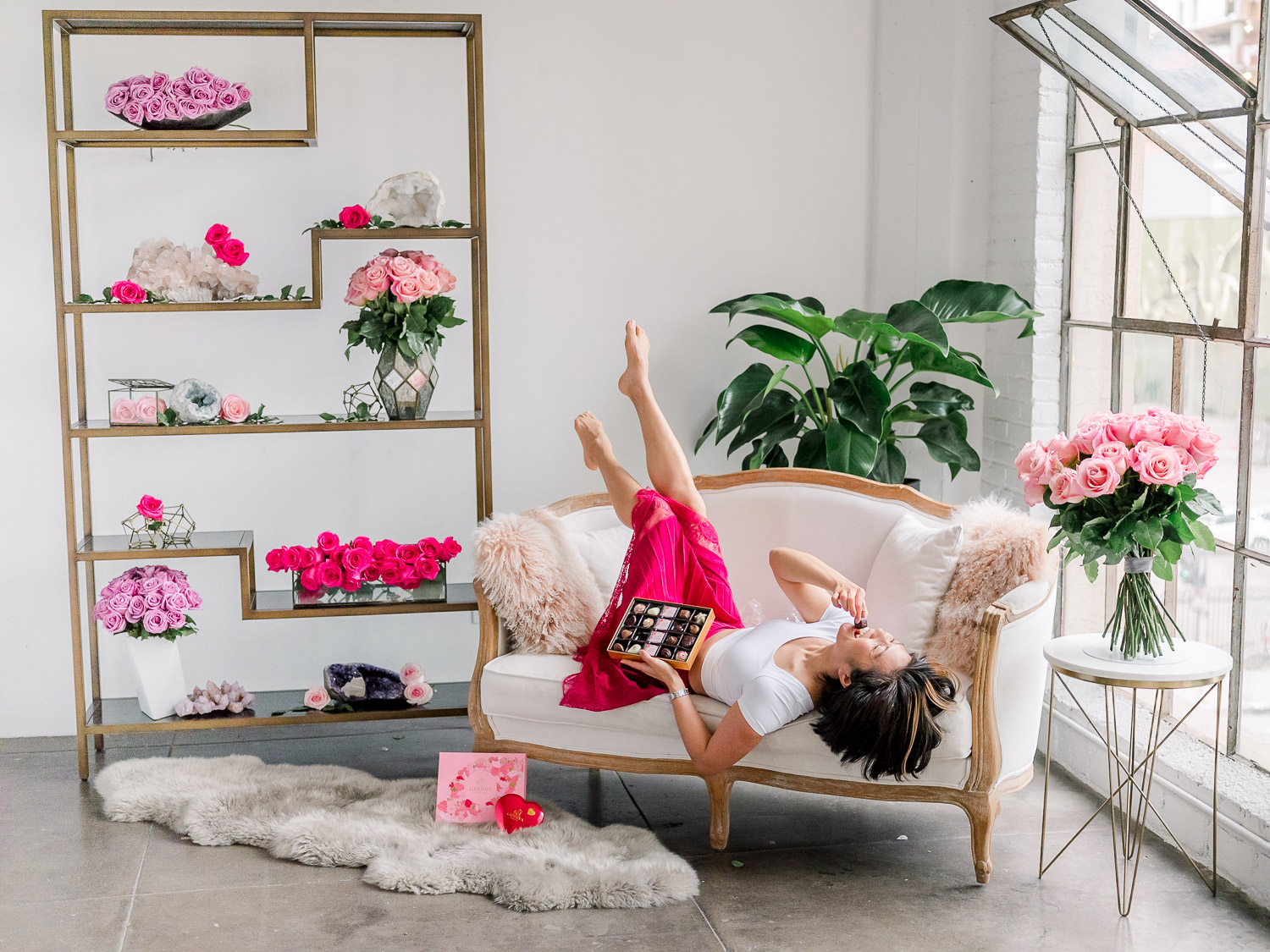 Caroline Tran laying on a couch, eating Godiva chocolates, surrounded by all shades of pink roses from enchanted express.
